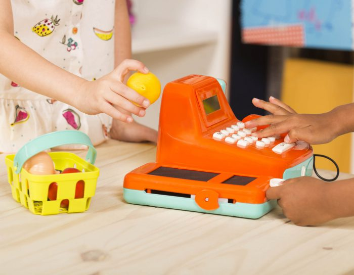 Kids fingers press on toy cash register button and a girl holds a lemon on the other side.