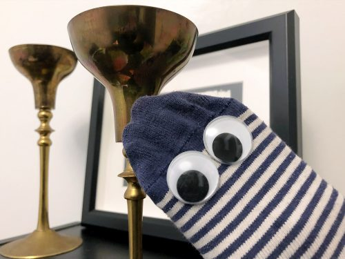 Sock puppet with googly eyes, dusting a candle holder.