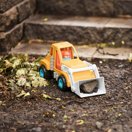 Toy front-end loader truck with a little driver, outside.