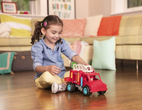 Smiling girl playing with toy fire truck.