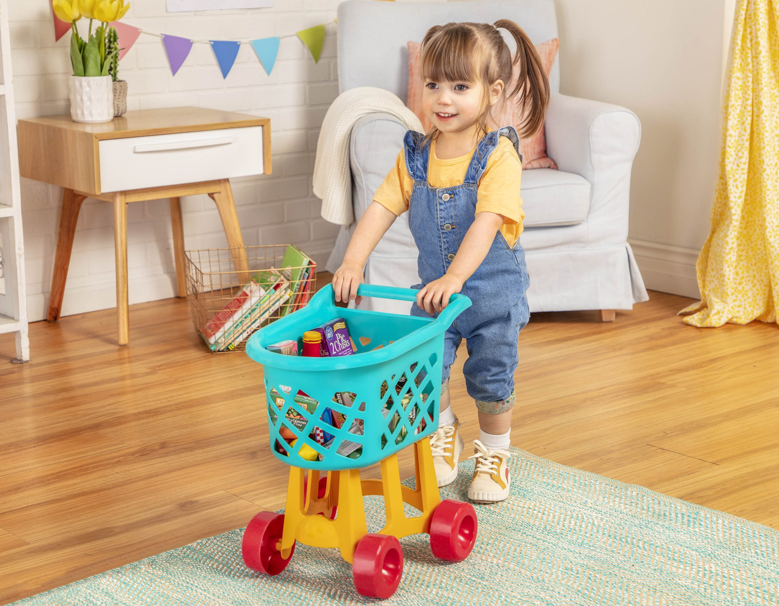 Smiling girl pushing a toy grocery cart with toy food inside.