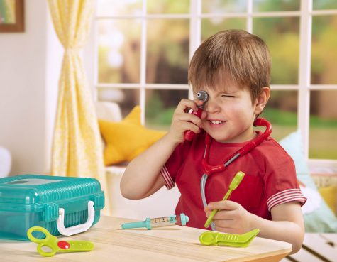 Boy playing pretend with a doctor kit and holding a toy ear checker.