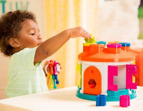 Boy putting a piece into a shape sorter house toy.