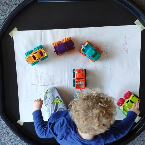 Boy drawing with trucks.