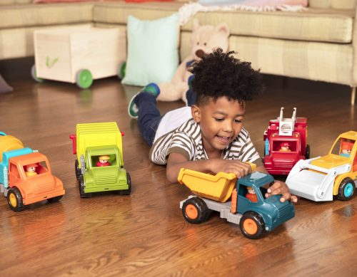 Boy playing with 5 different toy trucks on the floor.