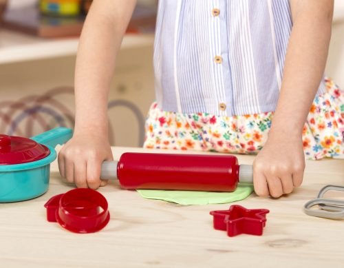 Close-up photo of girl holding a toy rolling pin and rolling out play dough.