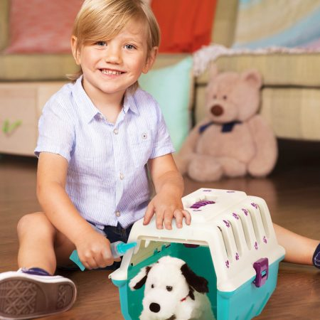 Smiling boy sitting next to a toy vet set with plush dog.