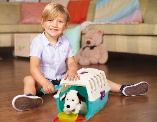 Smiling boy with toy vet set and plush dog.