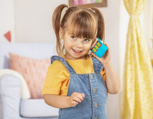 Smiling girl pretend talking on a toy cell phone.