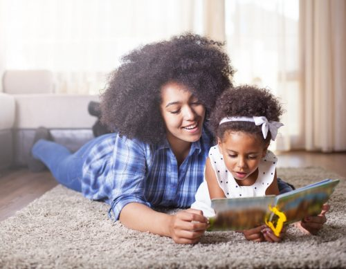 Mother and daughter reading book together.