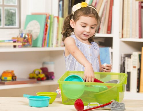 Child playing with toy cooking set.