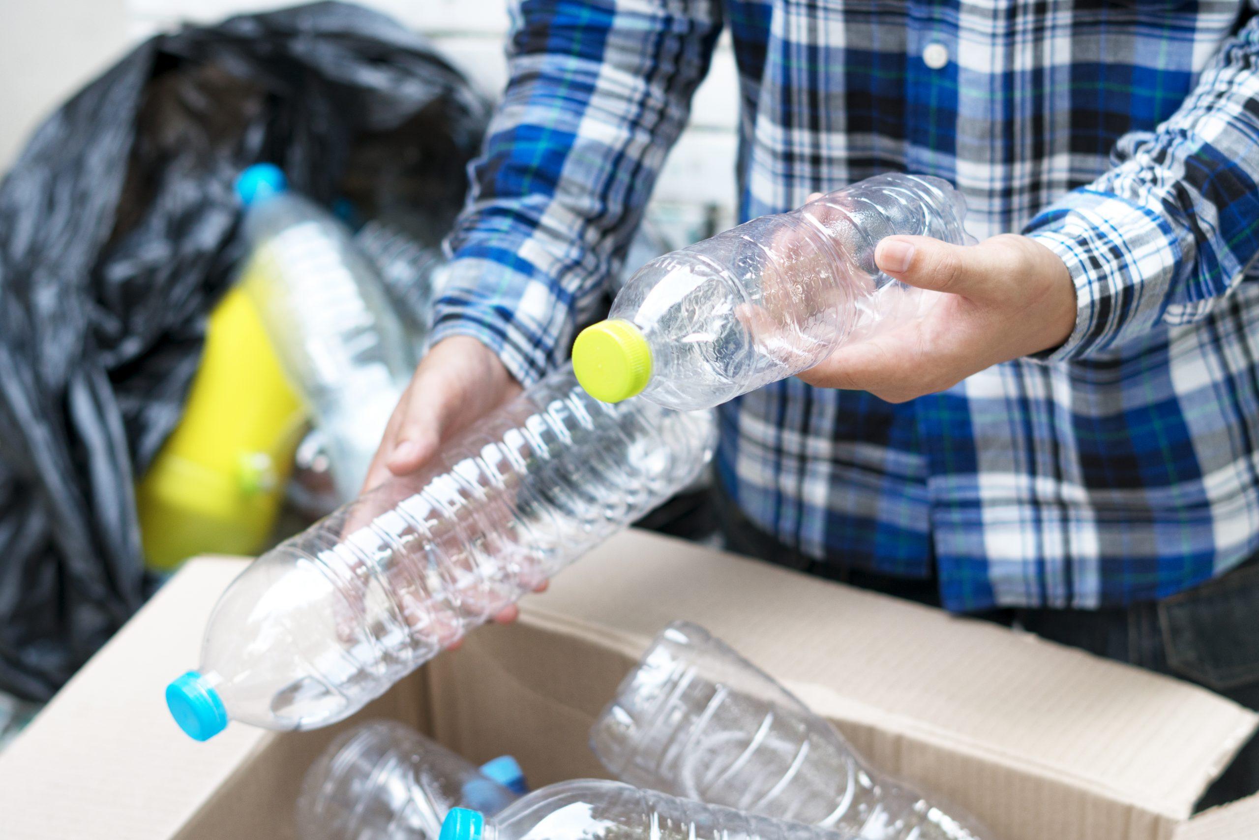 Person holding empty plastic bottles.
